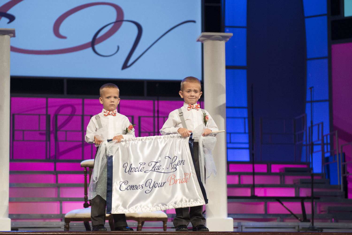 Ring bearers holding Here Comes Your Bride sign