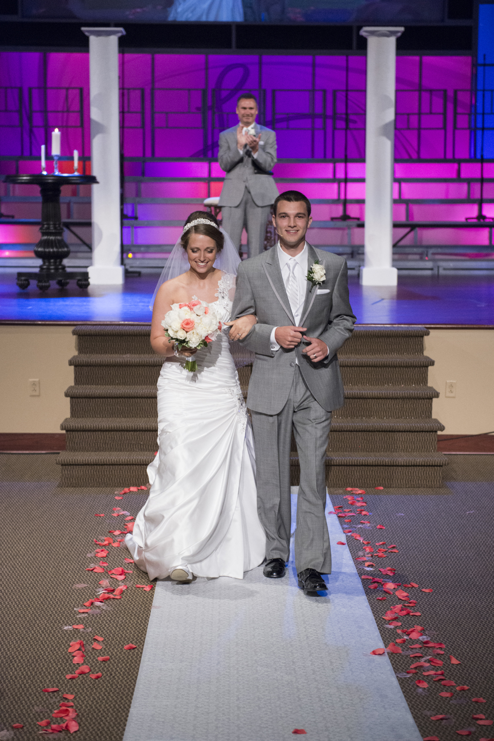 Bride and groom walking out of wedding during recessional in coral pink and navy