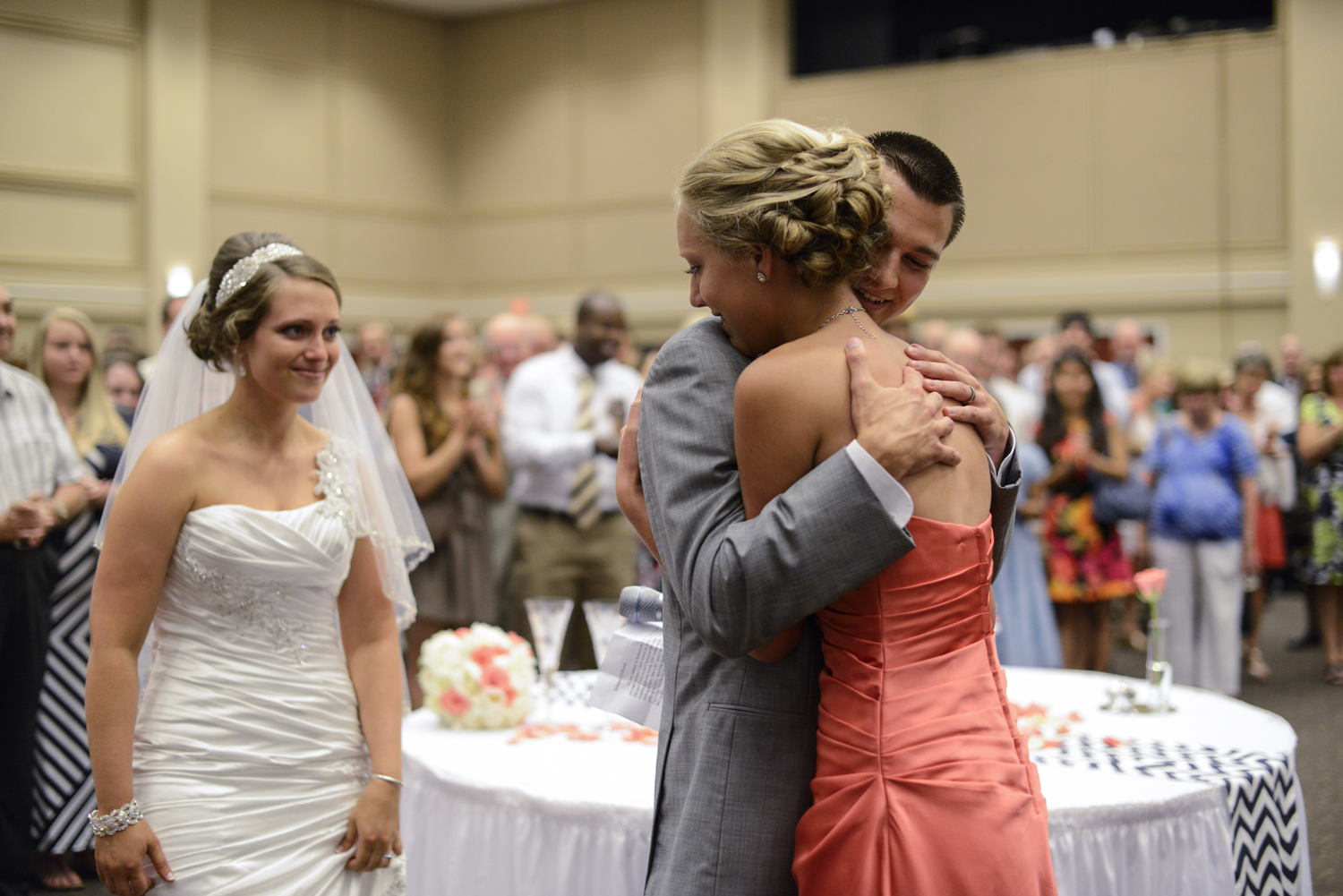 Groom and bridesmaid hugging after wedding toasts