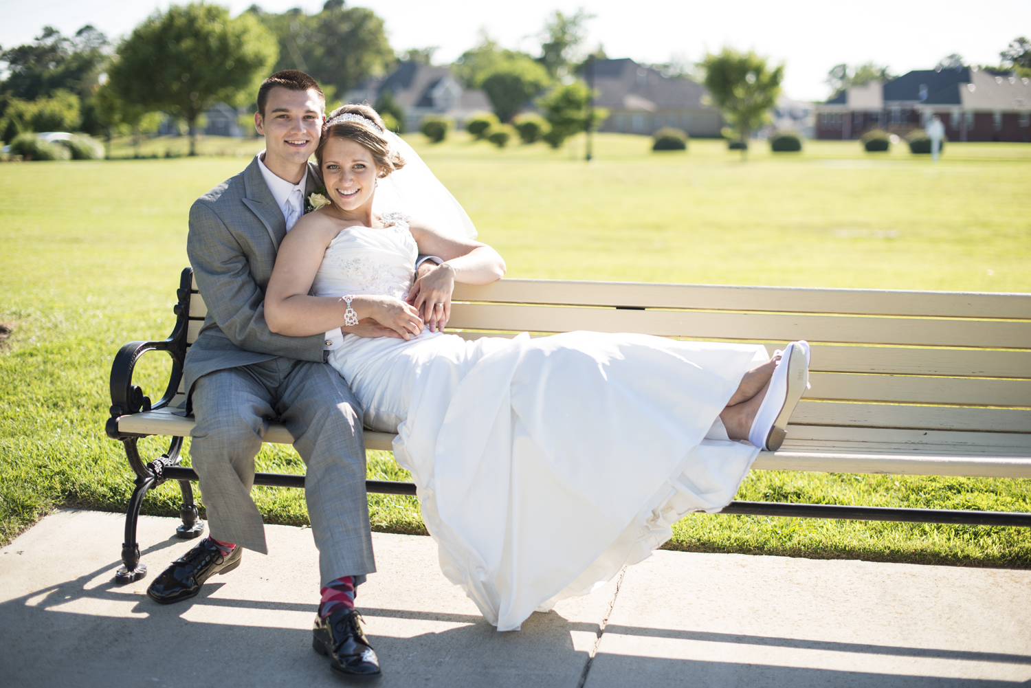 Bride and groom portrait on a bench by the water in Suffolk, Virginia