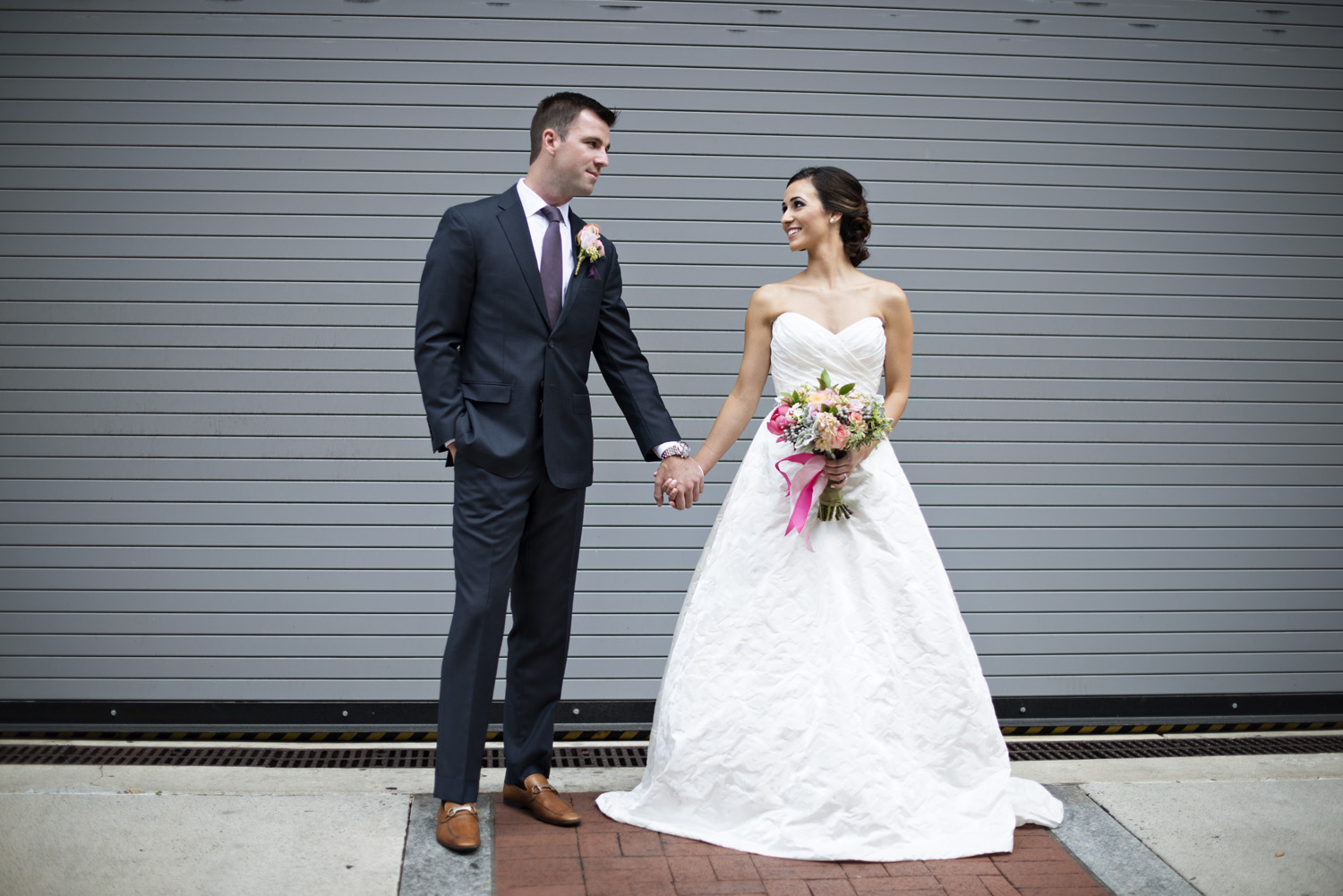 Washington, DC, wedding bride and groom portraits with pink hued florals