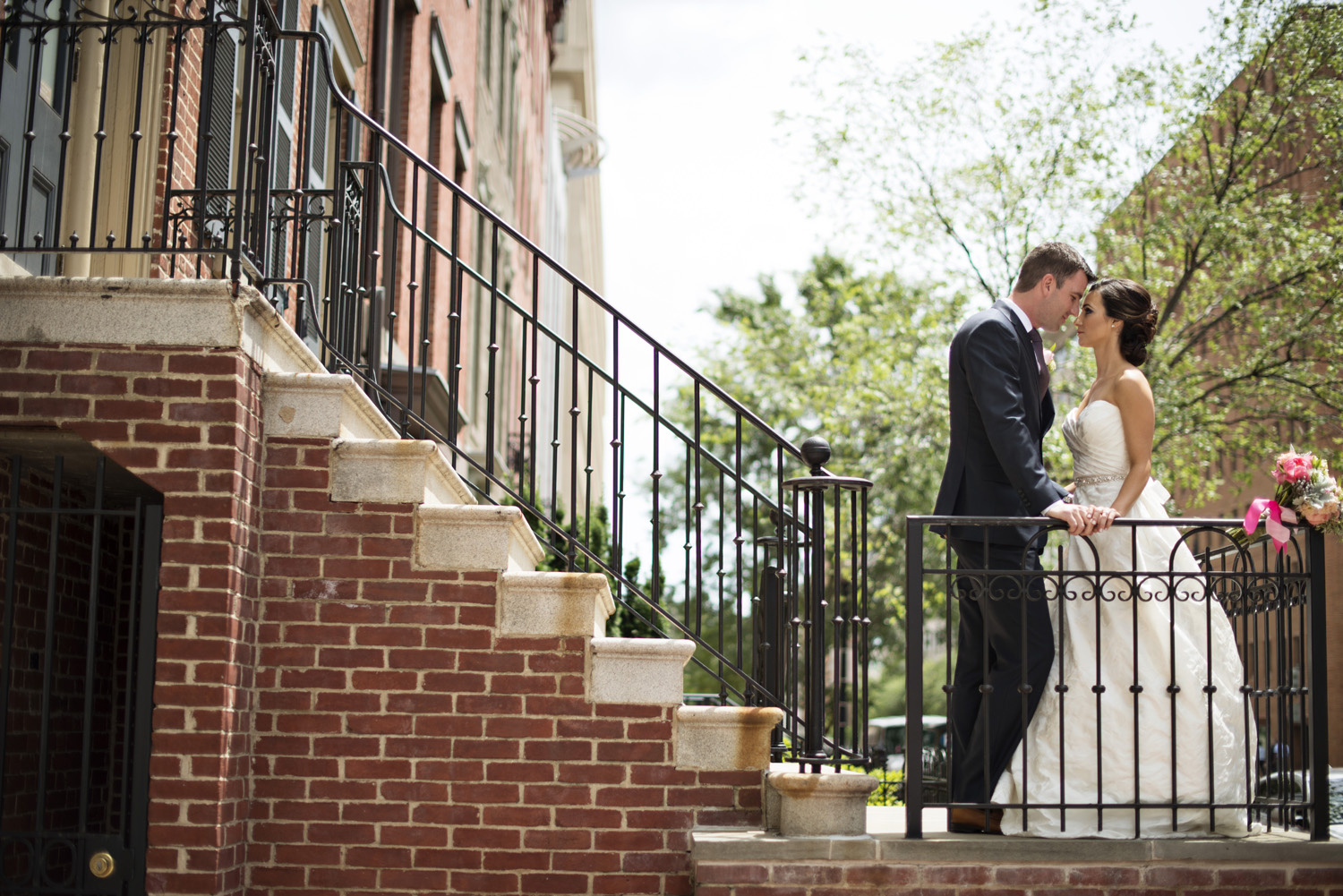 Washington, DC, wedding bride and groom portraits on a brick staircase with pink hued florals