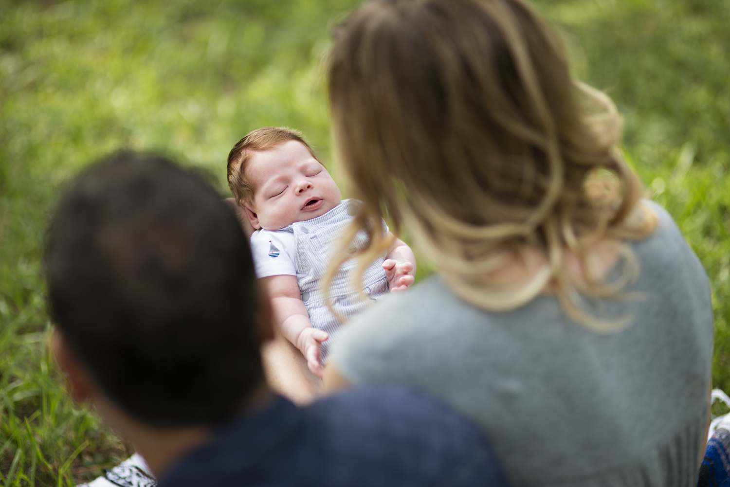 Mother and father gaze at their newborn baby boy during  family portraits on a picnic blanket in a park