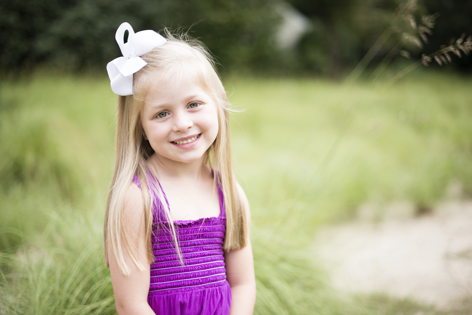 Little girl in a purple dress at Family portraits  at Princess Anne Country Club Golf Course in Virginia Beach