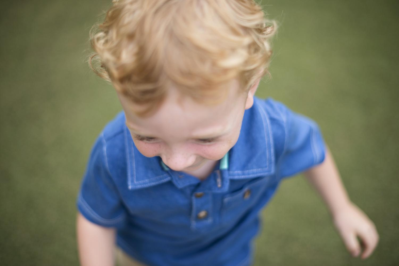 Precious little boy running on a golf course