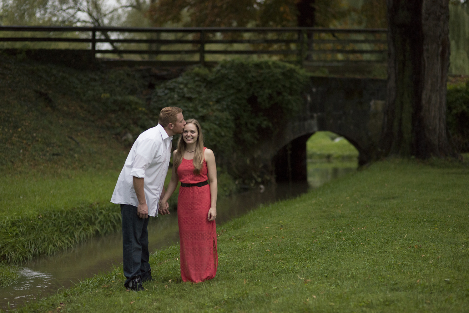 Kissing by a bridge at a  beautiful engagement pictures in Downtown Staunton, Virginia