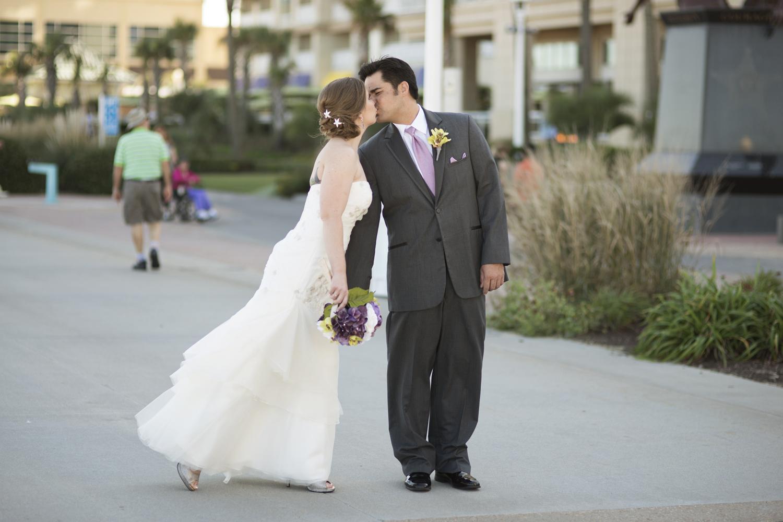 Bride and groom on beach boardwalk   Fall hotel wedding in Virginia Beach