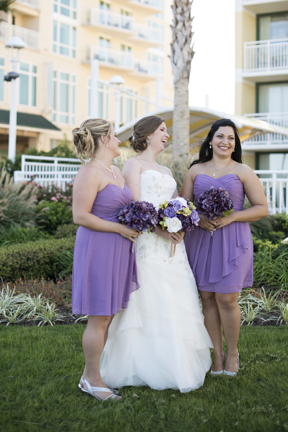 Bride and her bridesmaids in purple dresses with white flowers  | Fall hotel wedding in Virginia Beach
