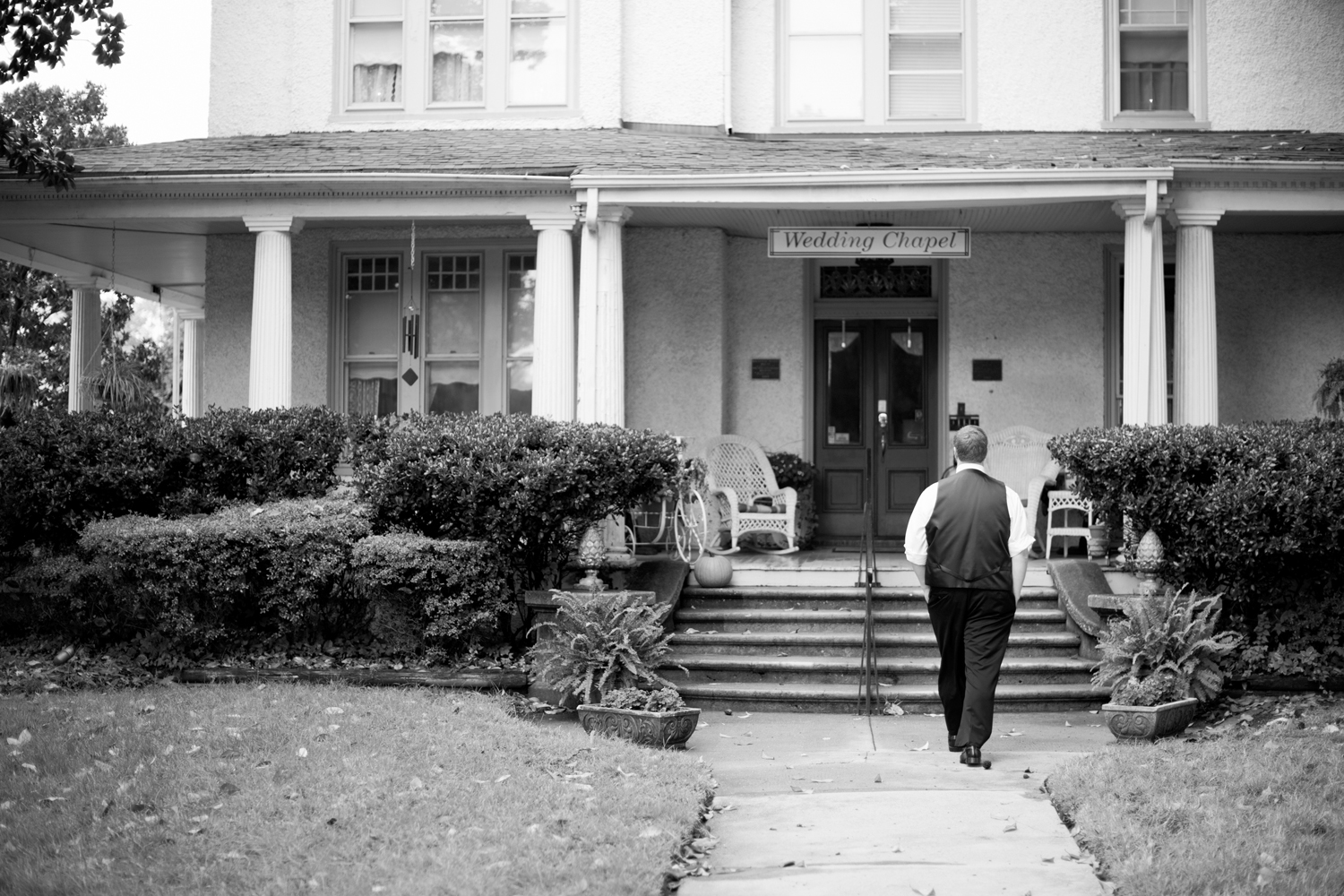 The groom walks back into the Magnolia House Inn in Hampton, Virginia, before he gets married (black and white)