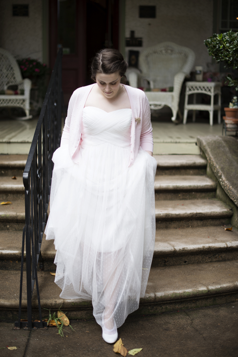 A bride walks down the steps in her pink cardigan at the Magnolia House Inn in Virginia
