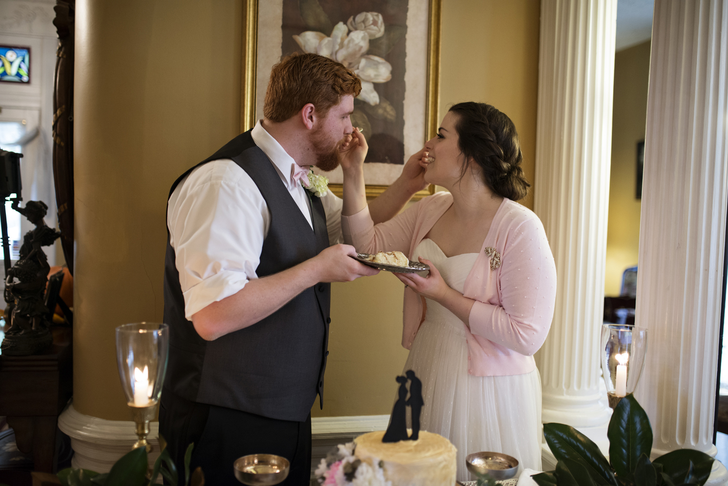 Bride and groom feed each other cake after they elope