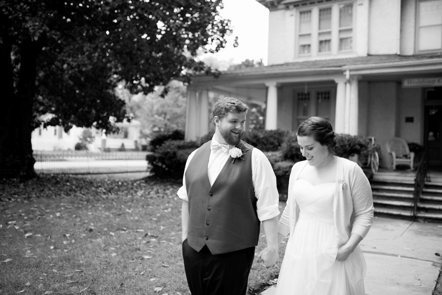 Bride and groom walk together outside a cute country house (black and white)