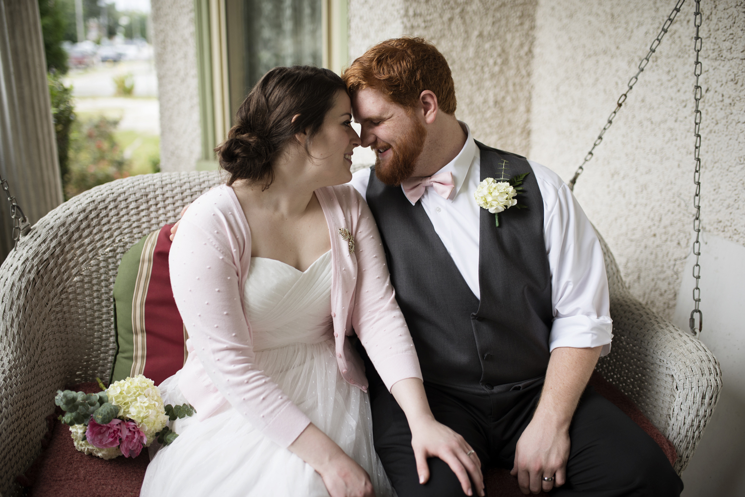 Bride and groom snuggle on a porch swing