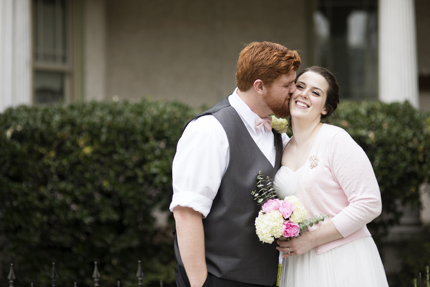 A groom kisses his bride, wearing a pink cardigan, on the cheek after their wedding