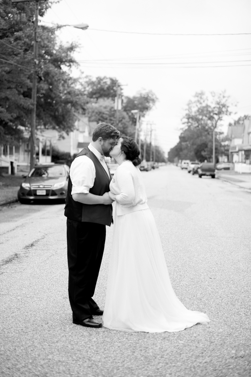 Bride and groom in a street in downtown Hampton kissing (black and white)