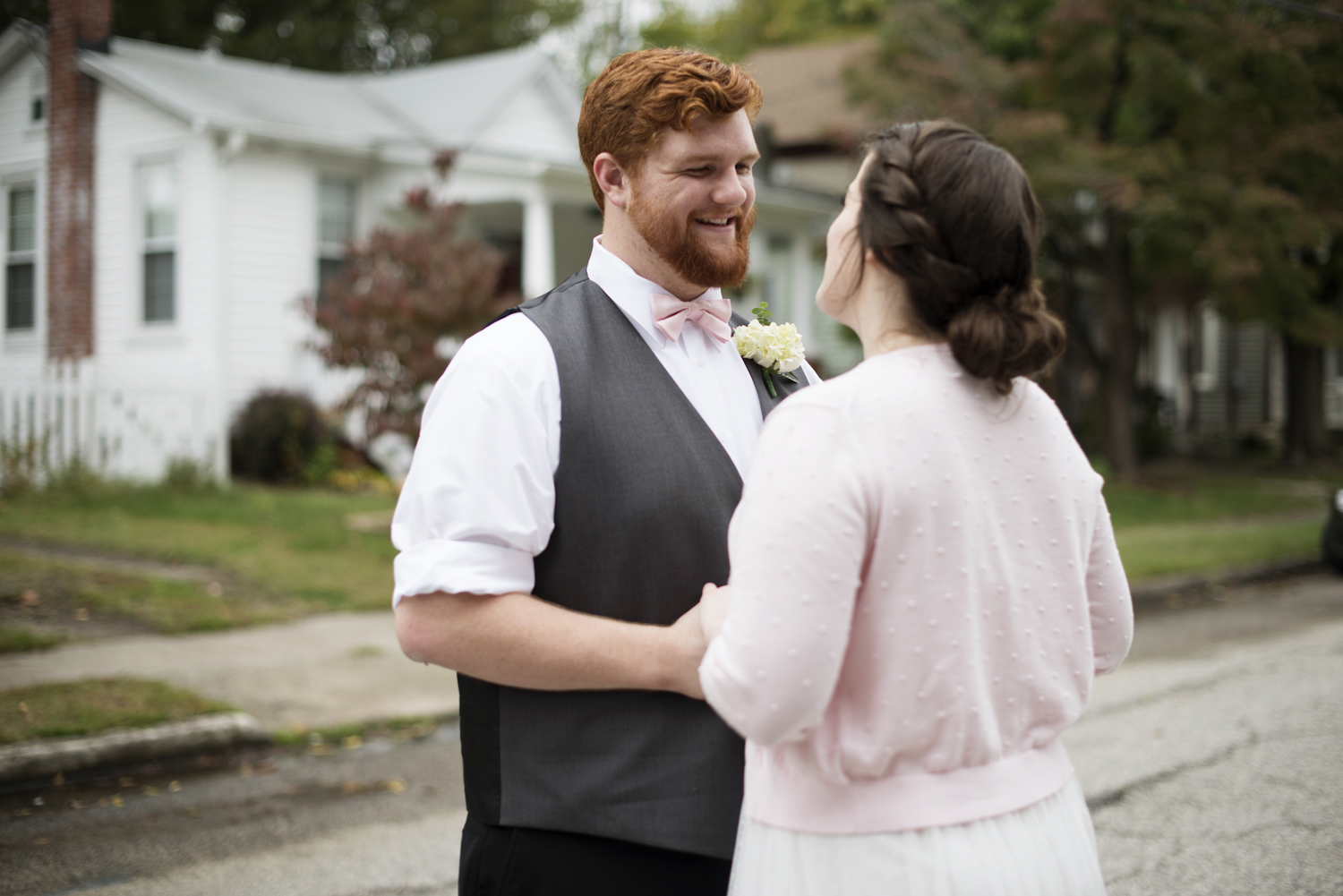 A groom smiles at his bride, wearing a pink cardigan, in downtown Hampton