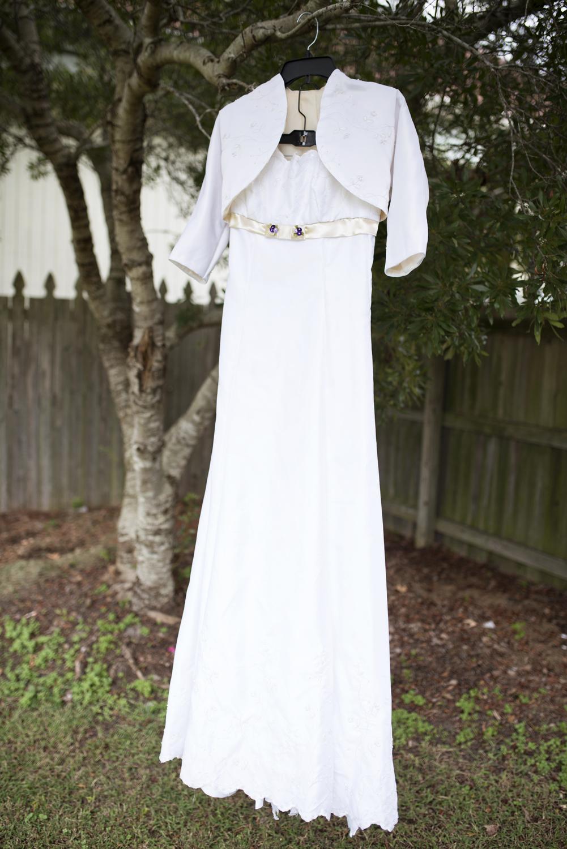 Handmade wedding dress hangs on a tree