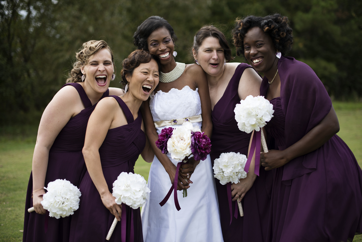 Bridesmaids in purple dresses with white flowers
