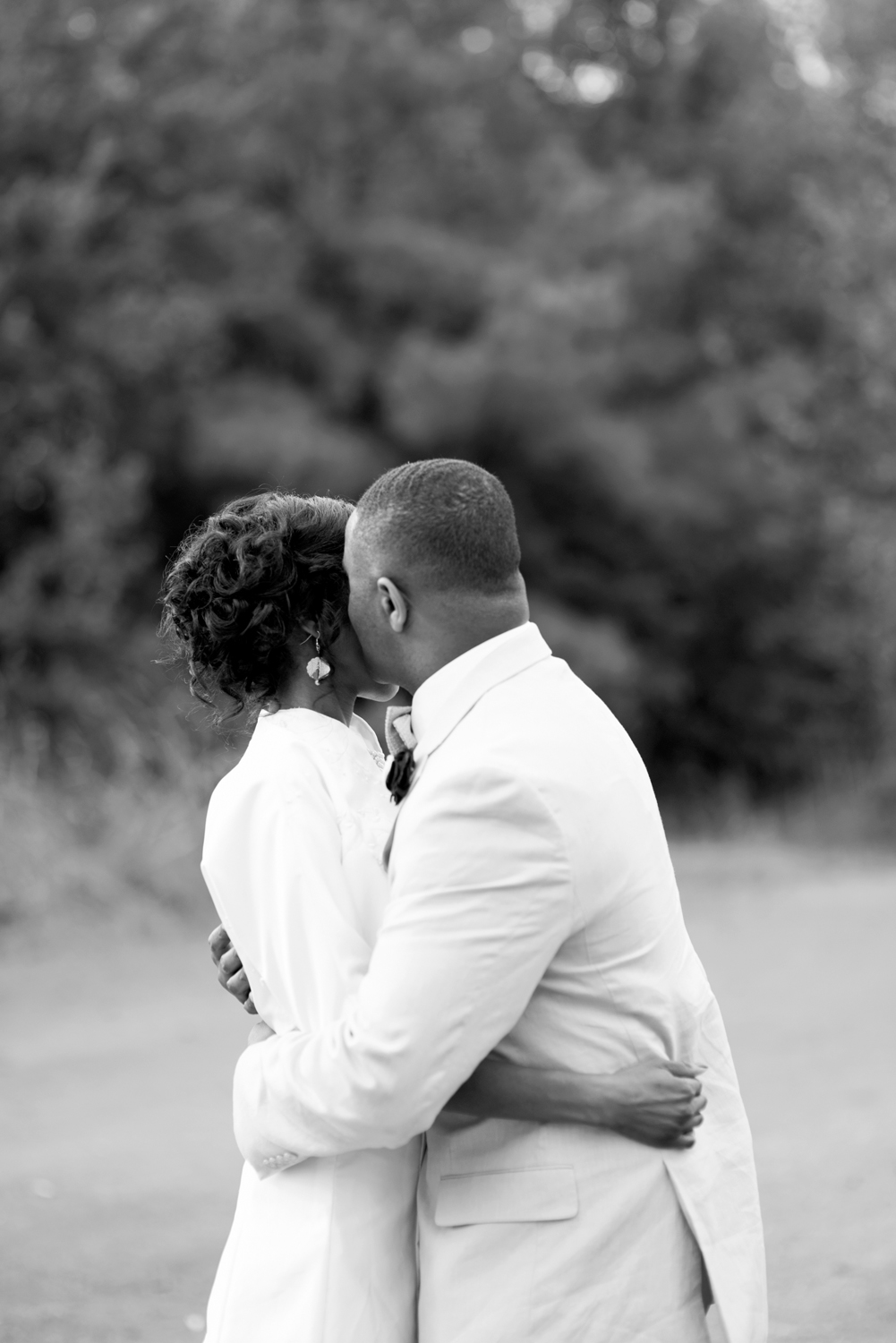 Groom whispering into his bride's ear (black and white)