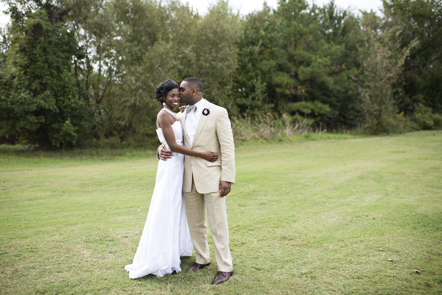 Groom kisses his bride on the cheek on a golf course in Virginia