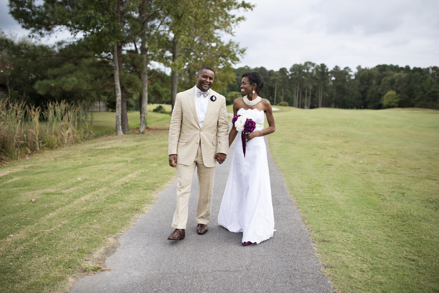 Bride and groom walk down a path together after their wedding