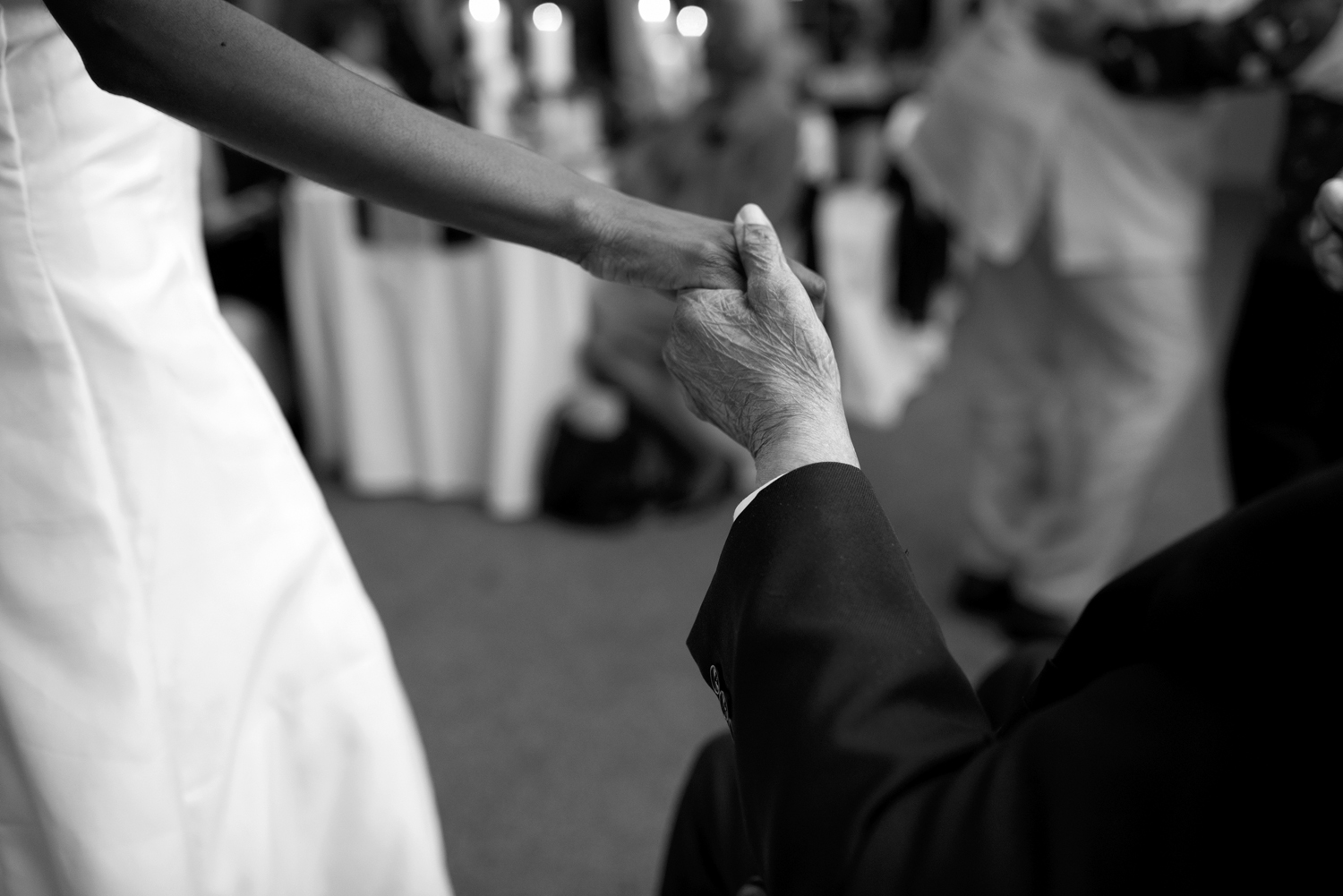 Bride holds her grandfather's hand at her wedding reception (black and white)