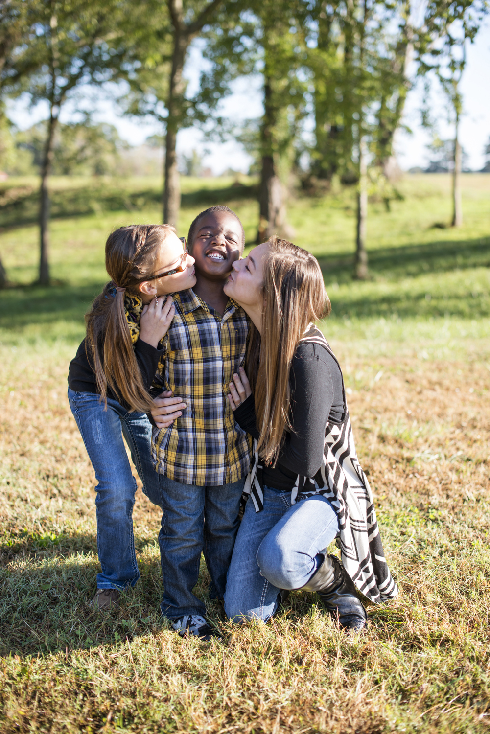 Girls kissing their brother's cheek during family portraits