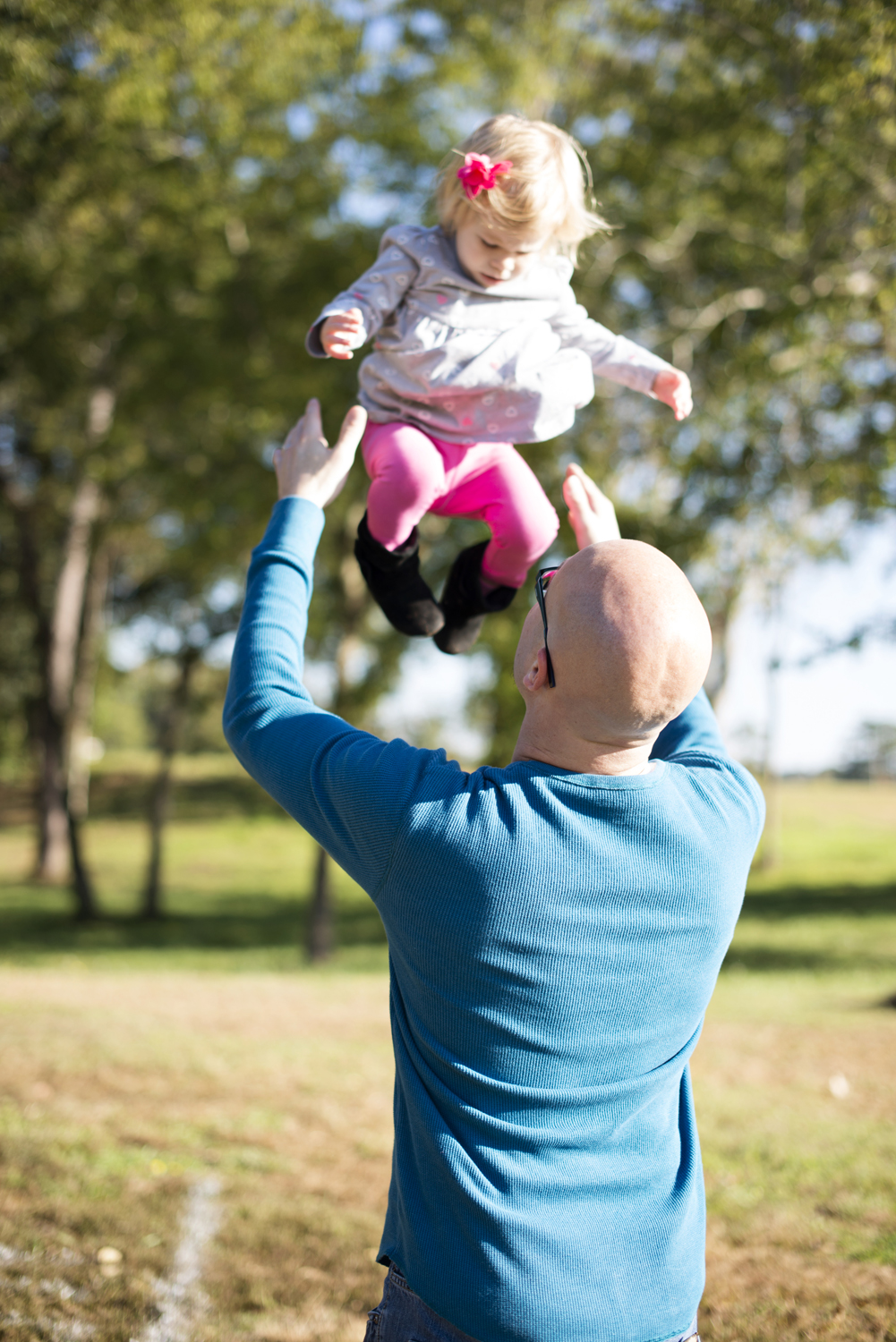 Dad throwing his daughter into the air