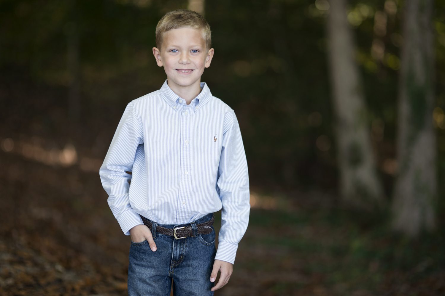Boy taking family pictures in the fall with jeans and a blue shirt