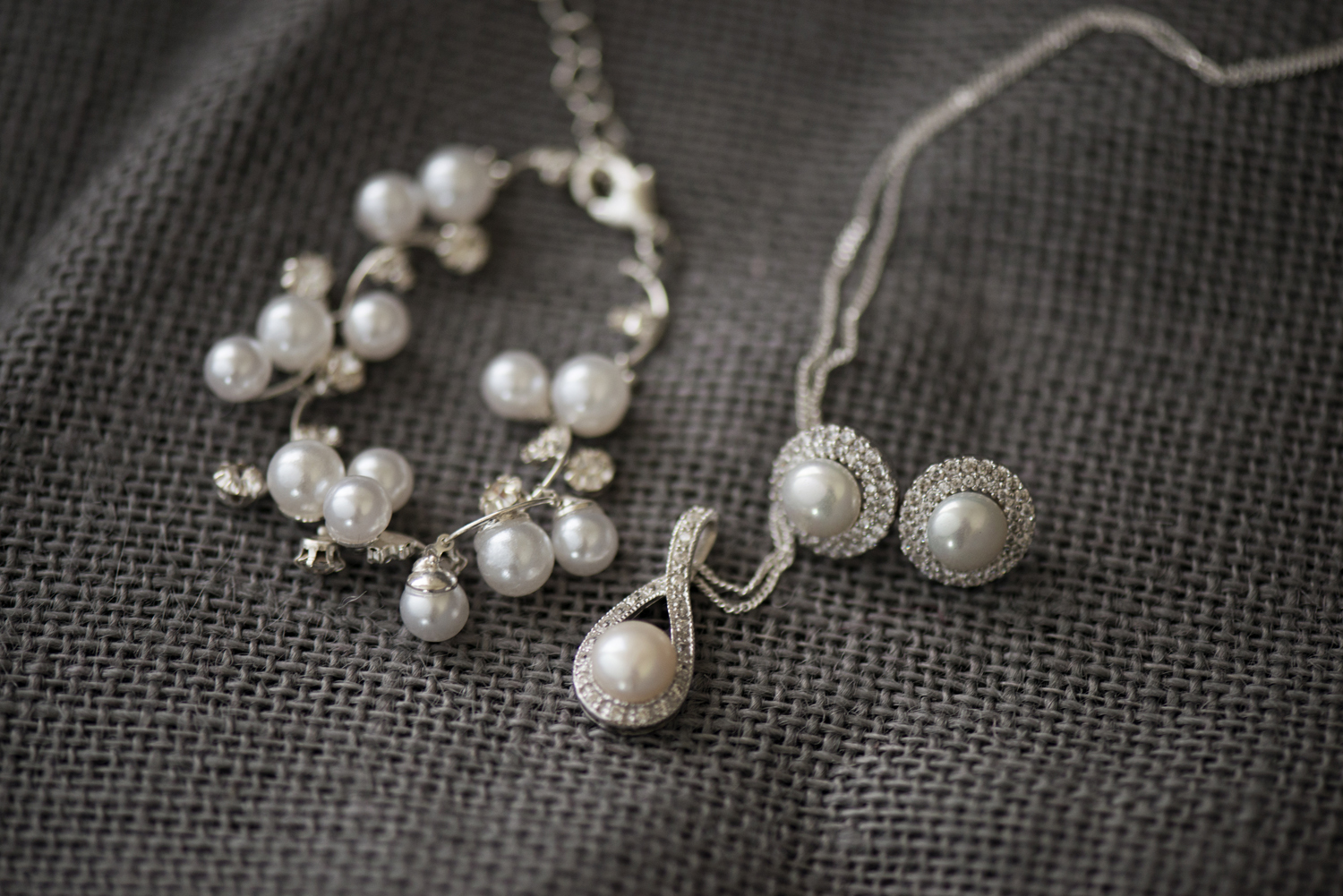 Pearl and diamond bridal jewelry on gray burlap