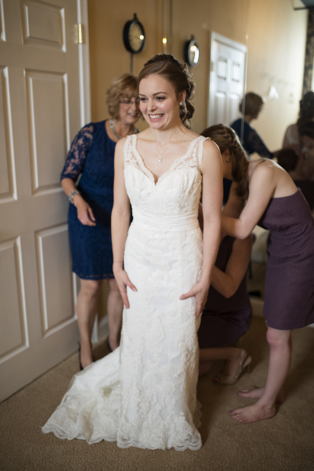 Bridesmaids in lavender dresses helping bride in lace wedding dress get ready