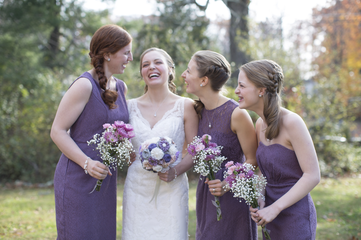 Bridesmaids in lavender dresses laugh with bride on her wedding day