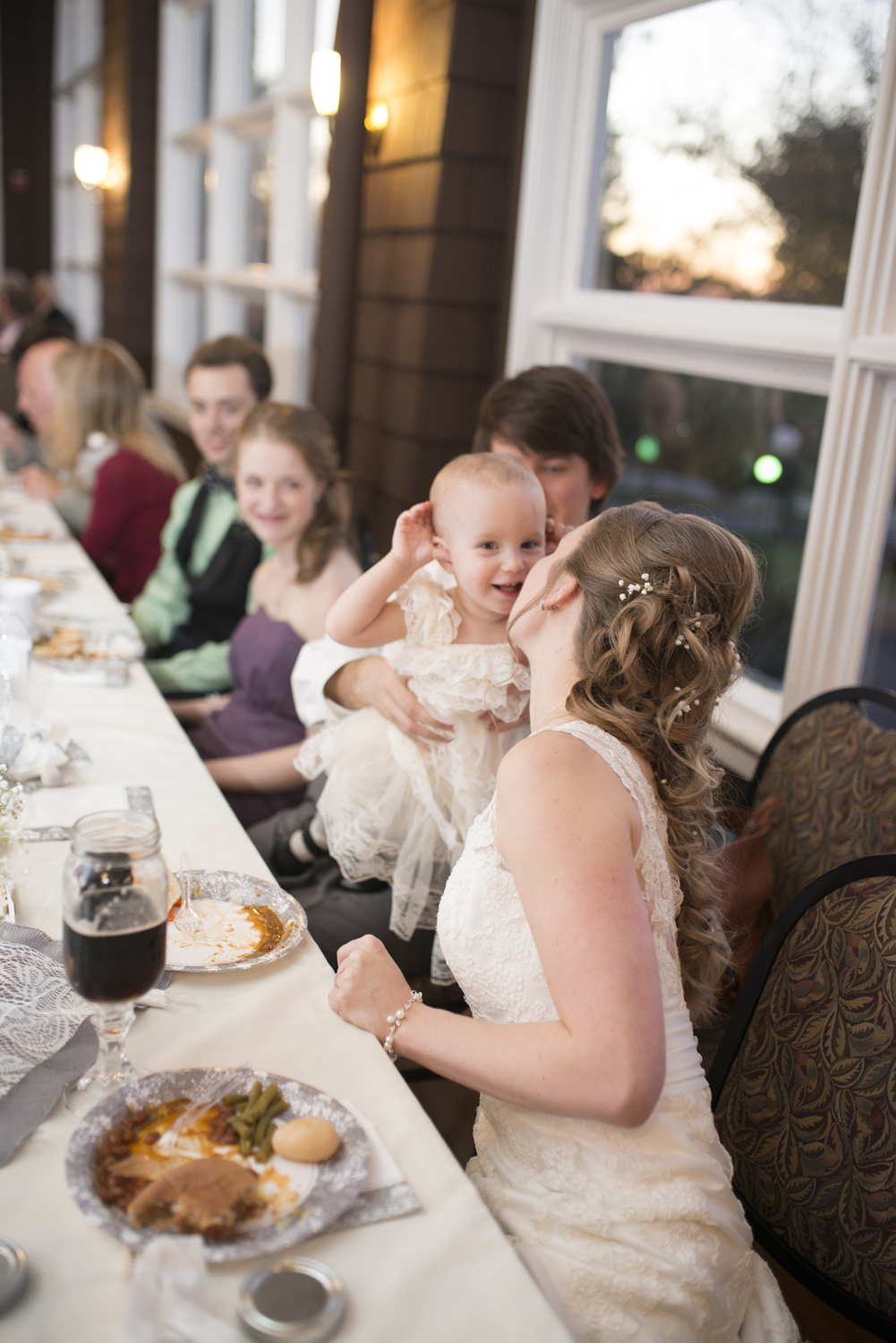 Bride kisses the flower girl at wedding reception