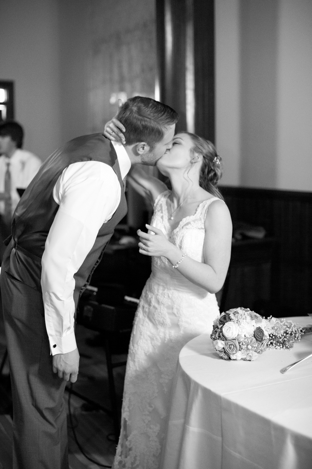 Bride and groom share a kiss by the wedding cake stand (black and white)