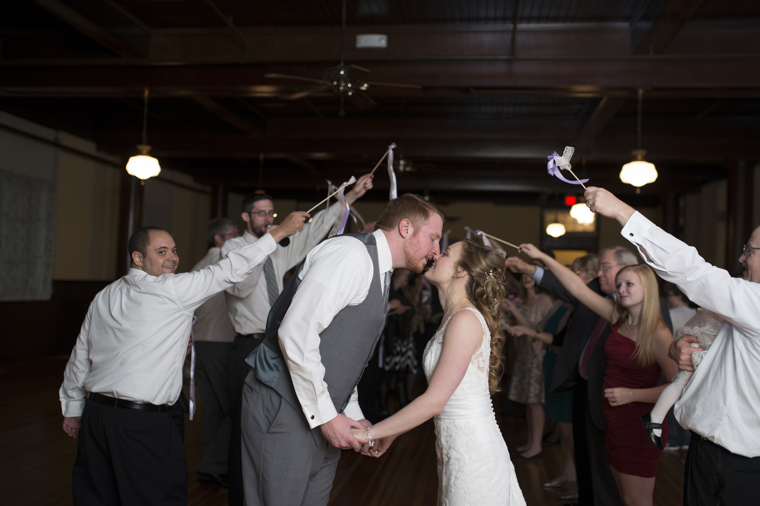 Bride and groom kiss during exit with party streamers