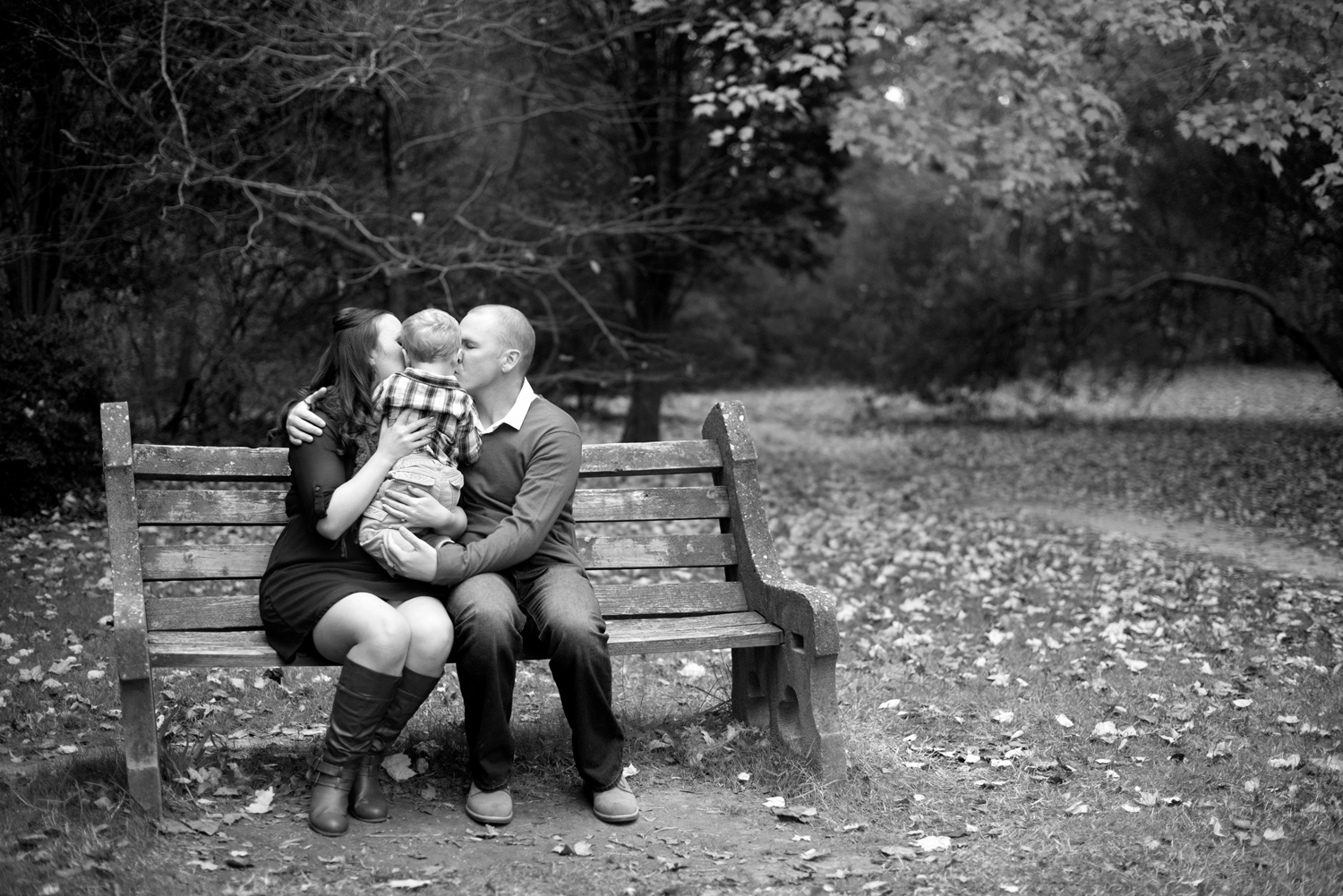 Mom and dad kiss baby on a park bench for fall family pictures
