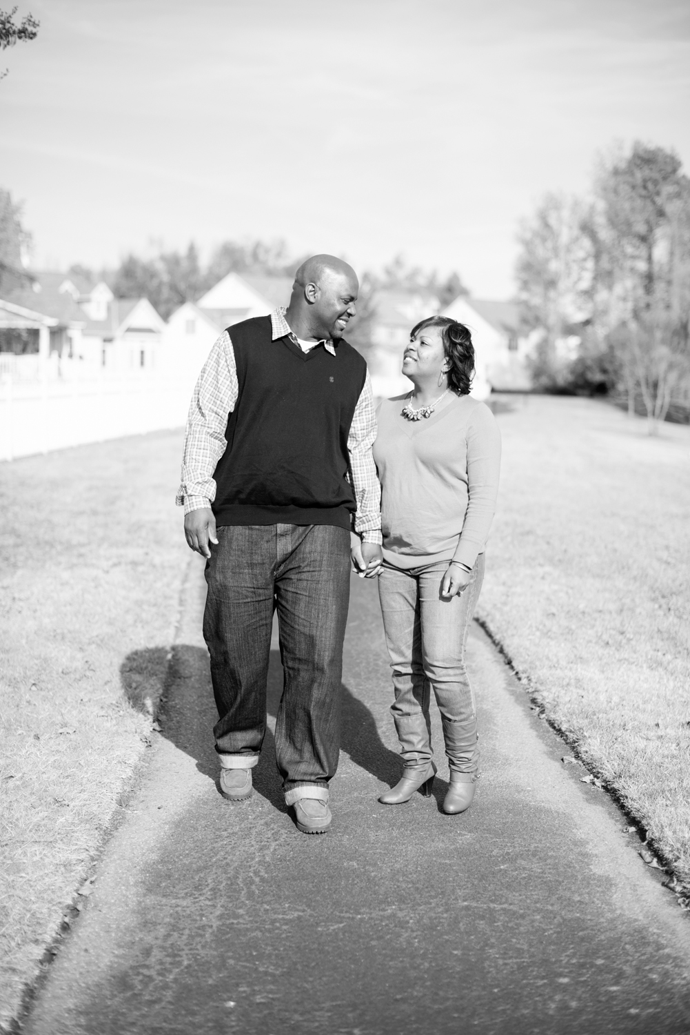 Husband and wife walk hand in hand on a paved path