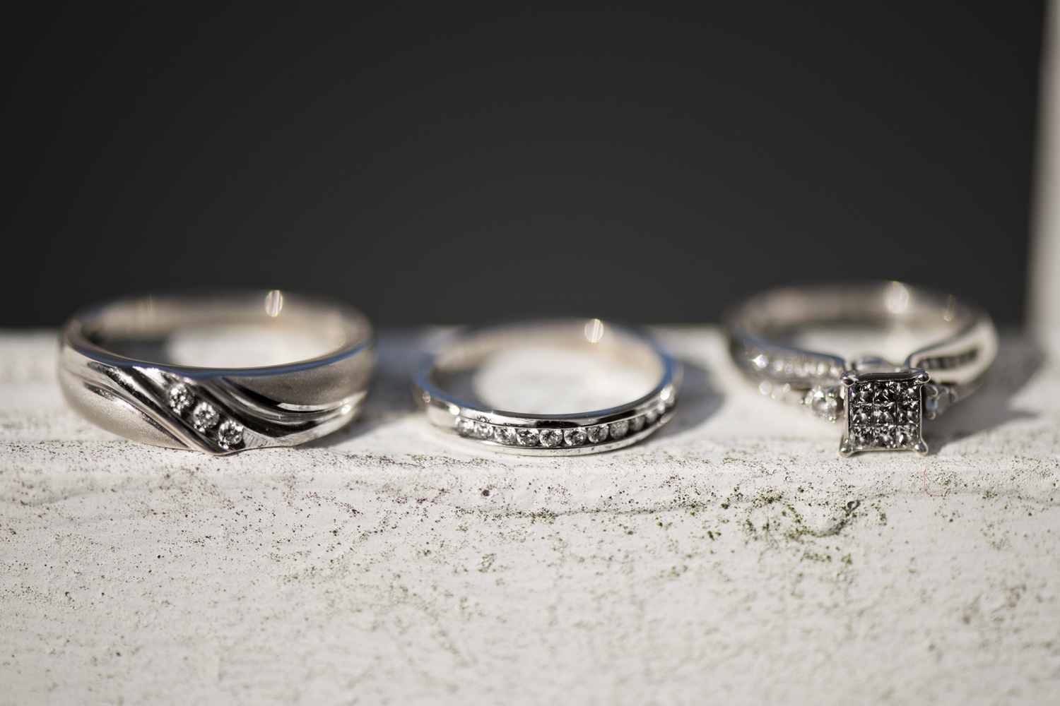 Wedding bands and engagement ring on a wood swing