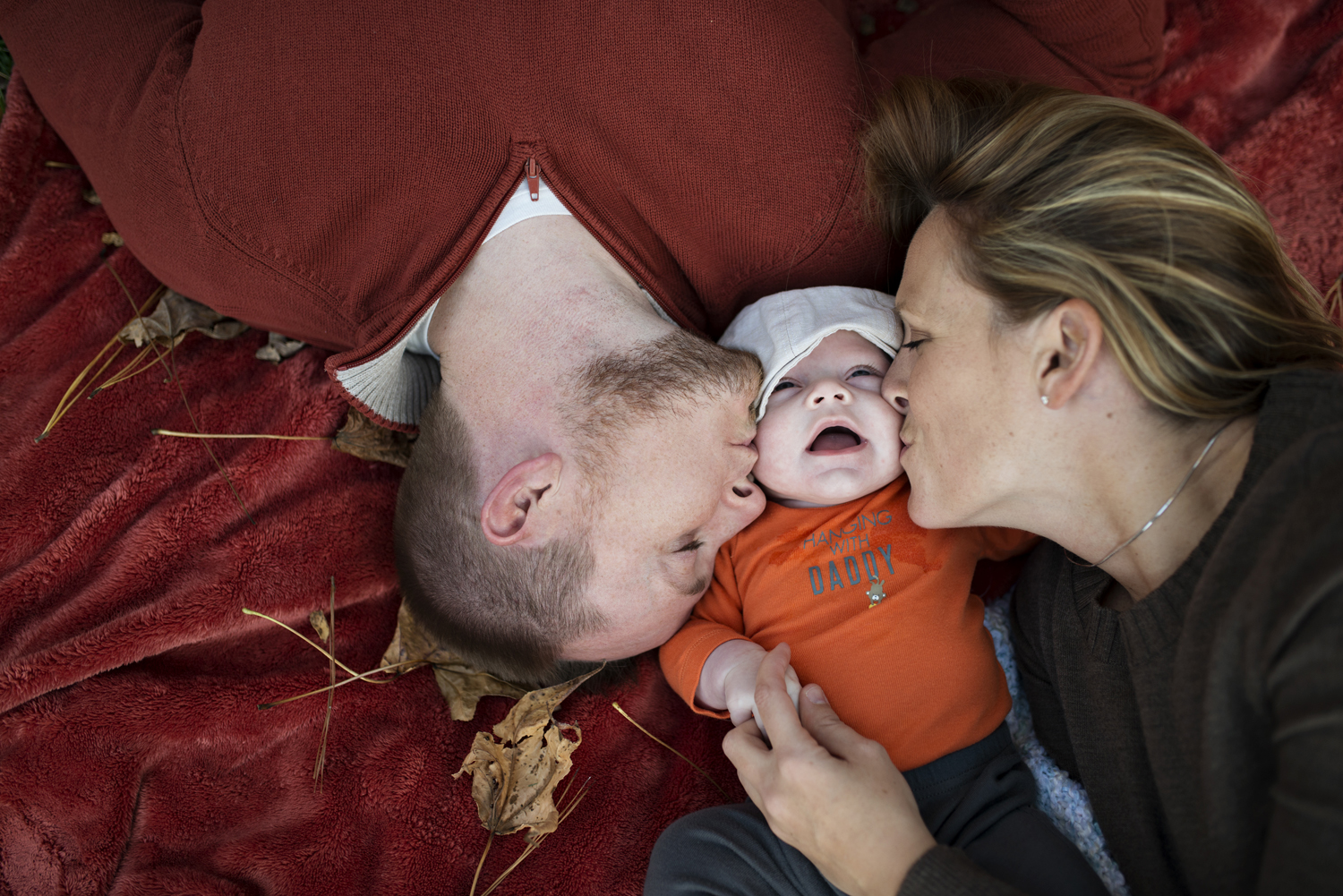 Cute family pictures on a red blanket in the fall