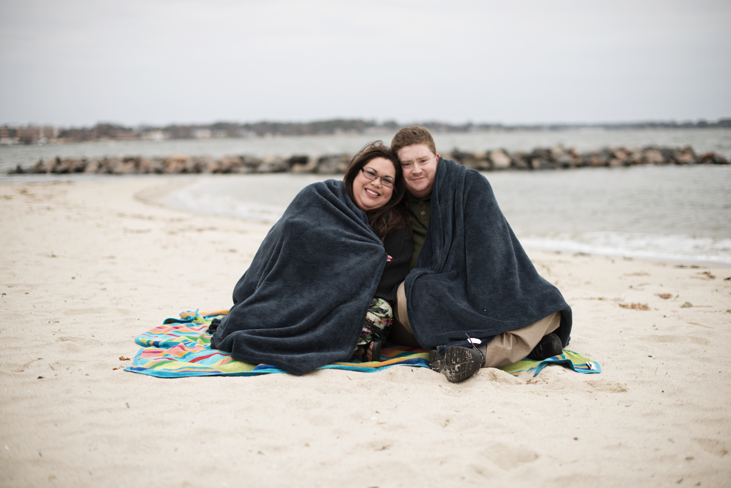 Beach engagement session posing ideas with a blanket