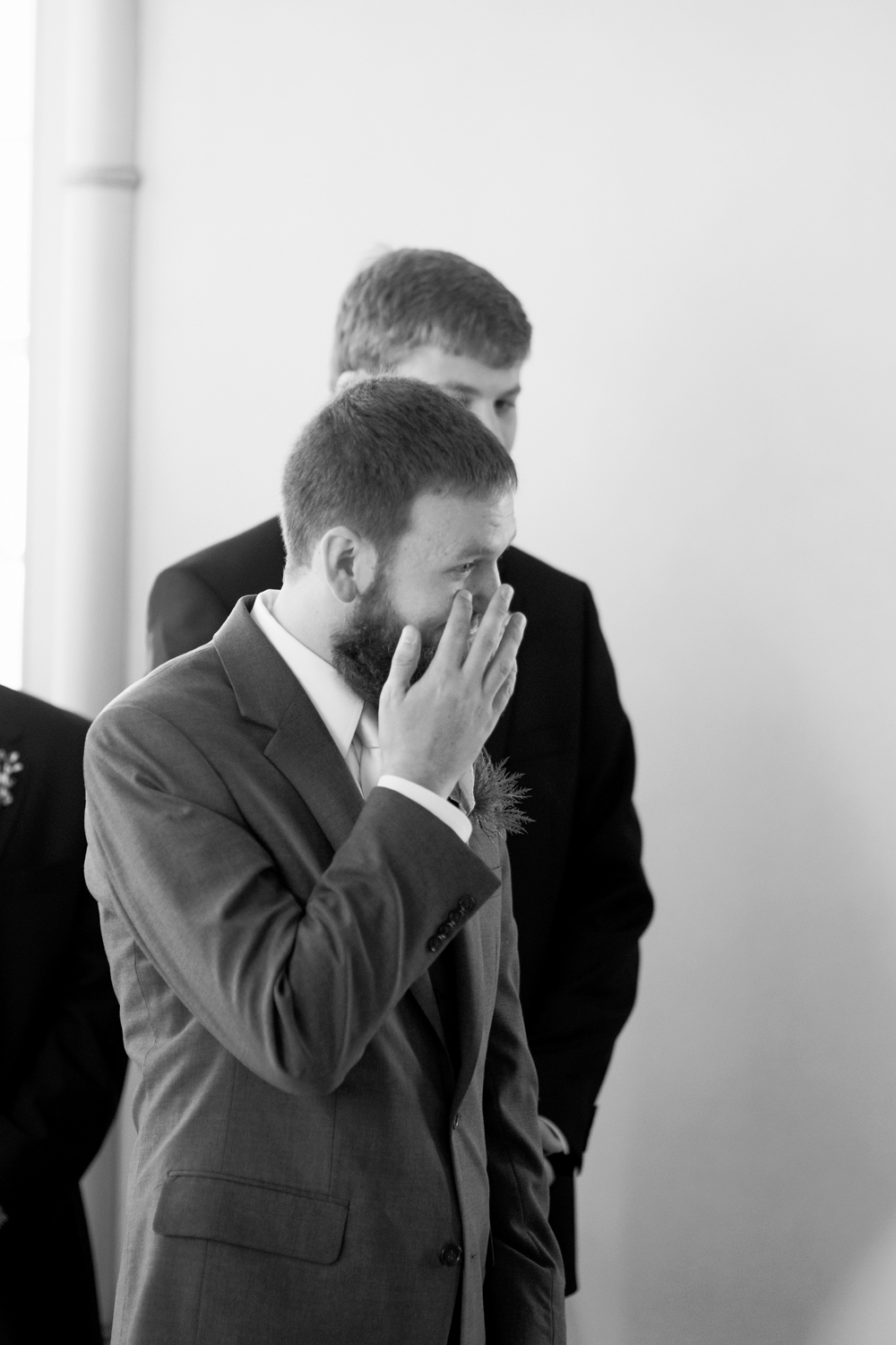 Groom wipes a tear from his cheek as his bride walks down the aisle