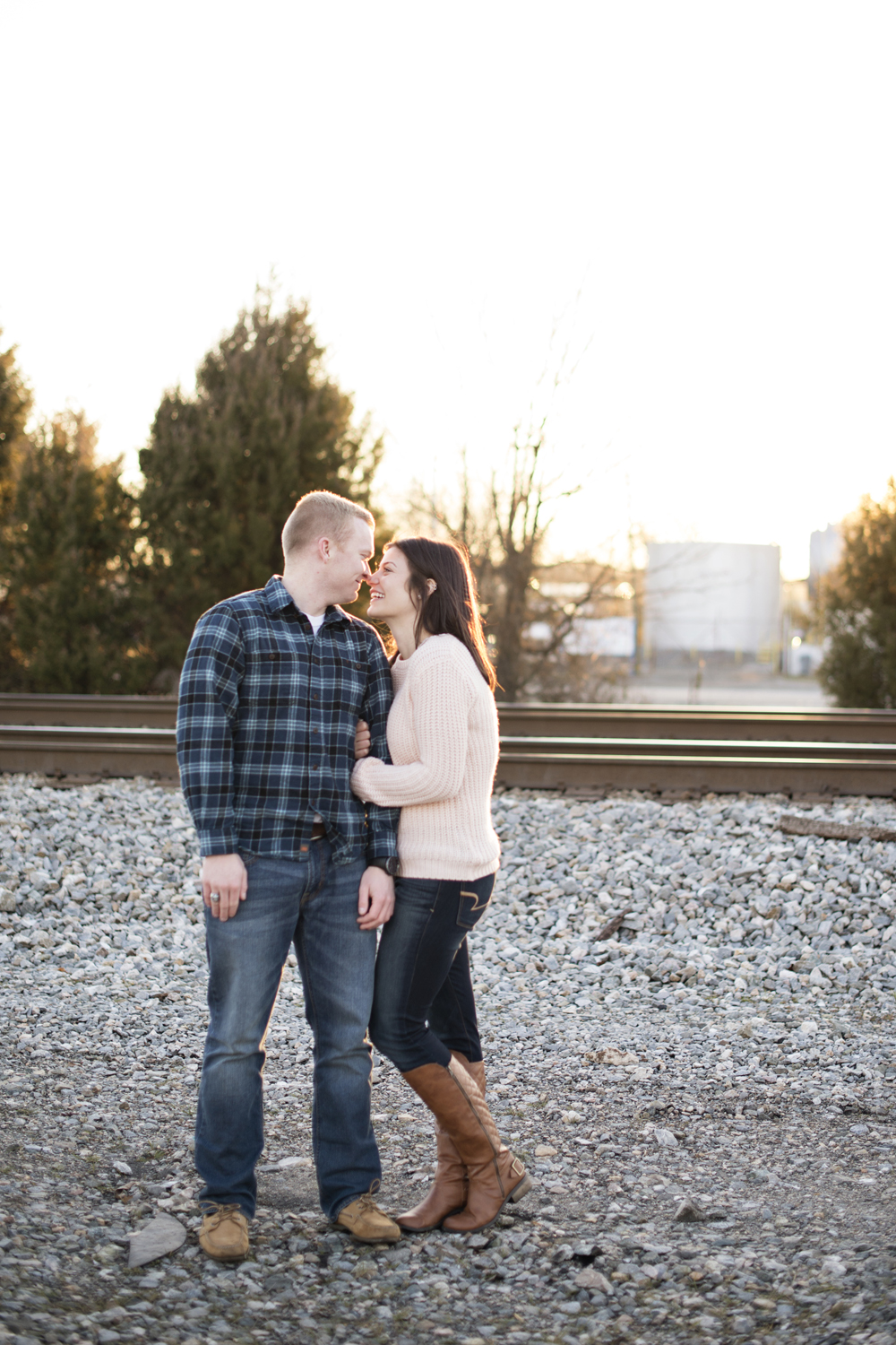 Sunset engagement pictures by train tracks during golden hour