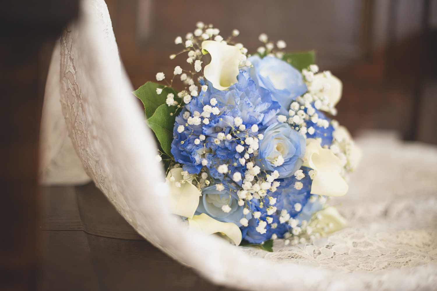 Wedding bouquet with white calla lilies, blue carnations, and baby's breath