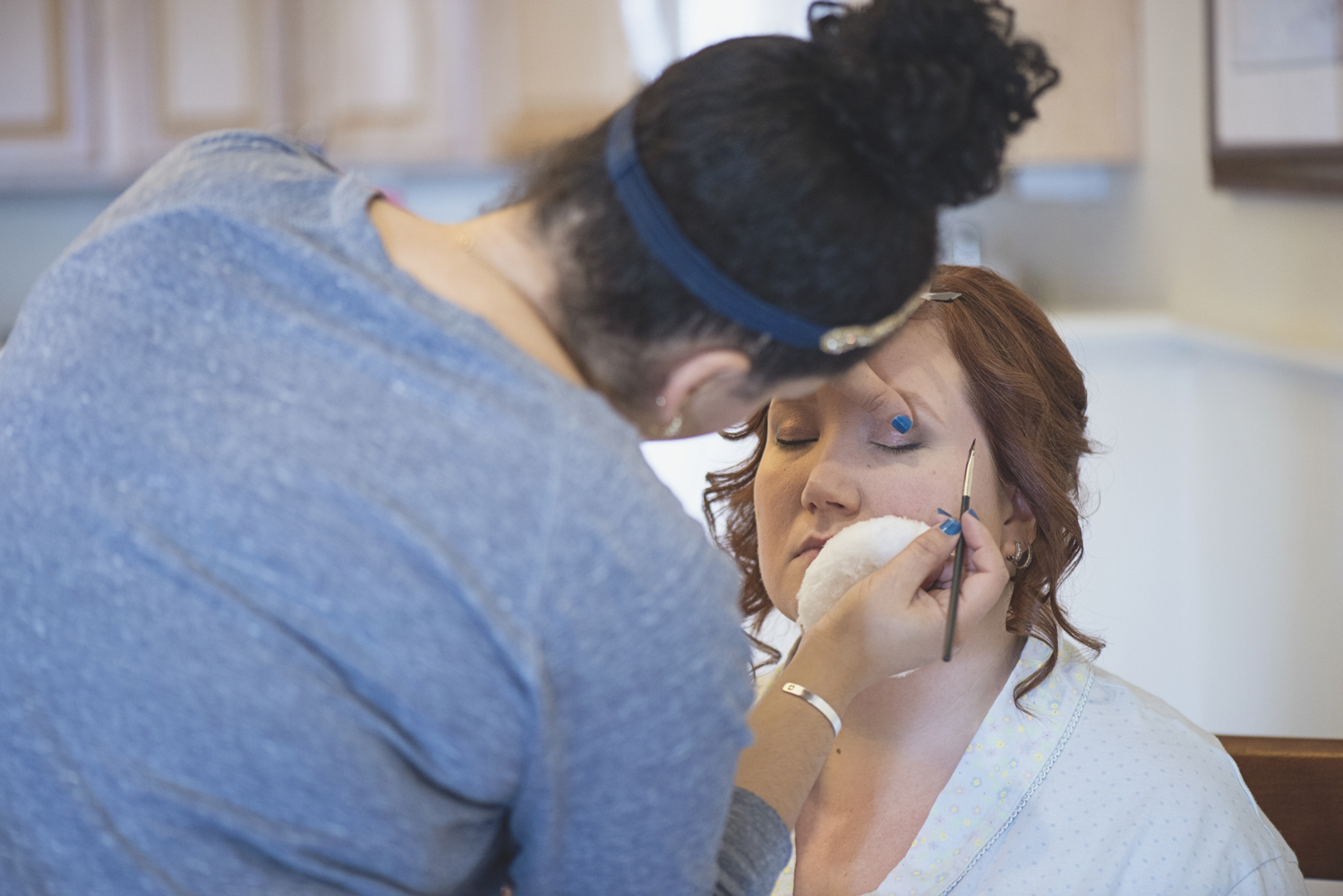 Bridesmaid getting her makeup done for a wedding