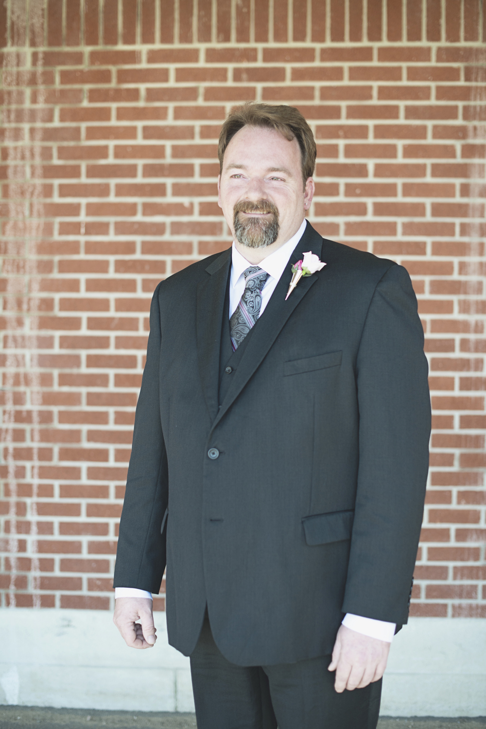 Groom portrait in front of brick wall
