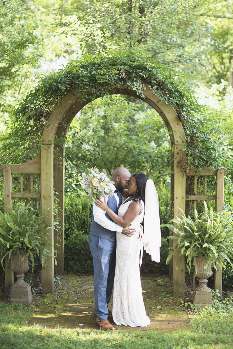 Elegant Lavender Plantation Elopement | Bride + groom portraits under greenery arch