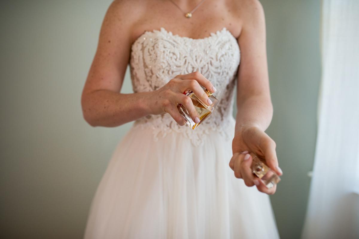Navy, Wine, and Gold Charleston Wedding | Bride putting on perfume