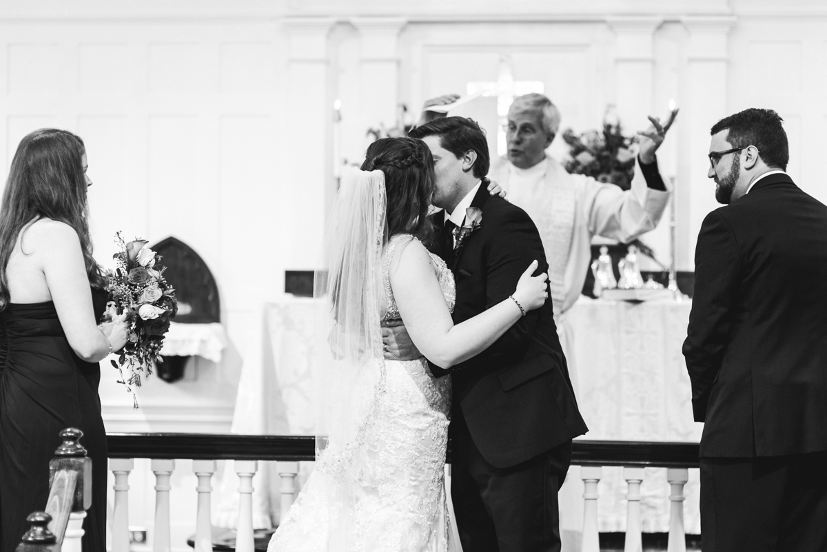 Gold, Blue, and Burgundy Fall Wedding | Bride and groom first kiss