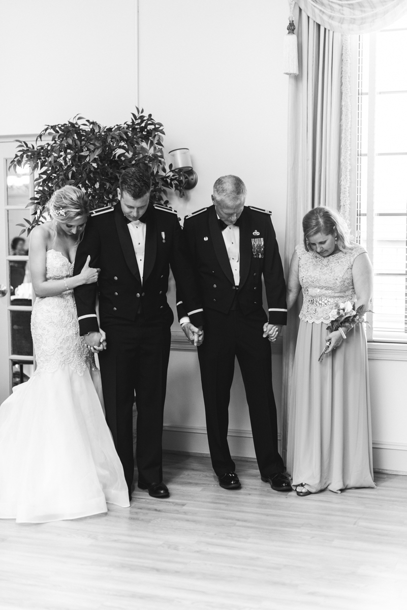 Blush and Gold Military Wedding | Parents praying with bride and groom