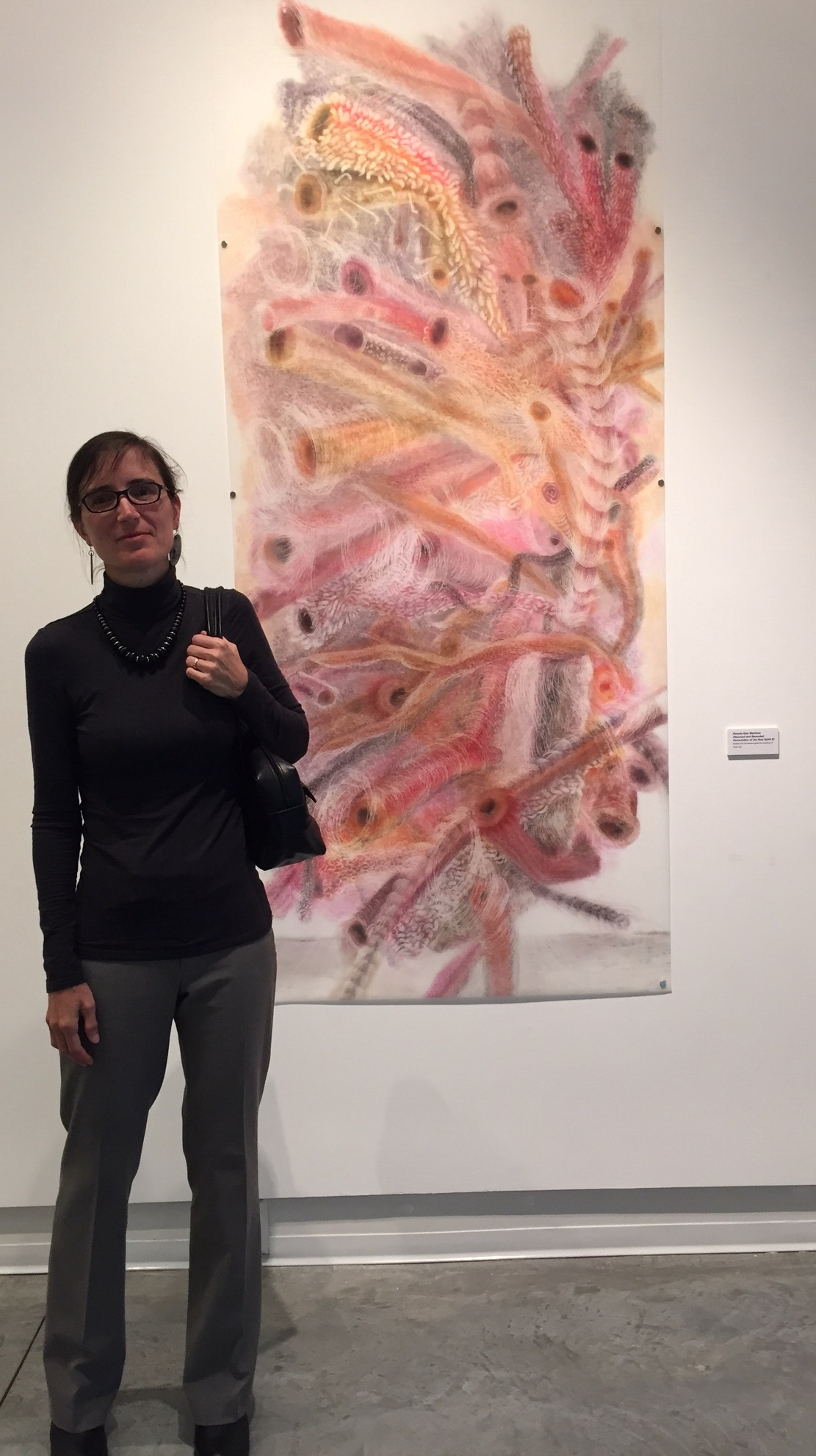 Artist Milada Pisoncikova standing in front of my pastel erasing. Title:  Observed and Recorded Permutation of The Holy Spirit XI  (40 inches x 79.5 inches-pastel and powdered graphite erasing on dura-lar)